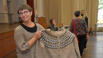 Nina Nurminen håller upp en tröja hon stickat.