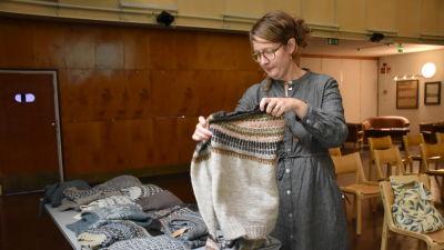 Erika Åberg håller upp en tröja som hon stickat.