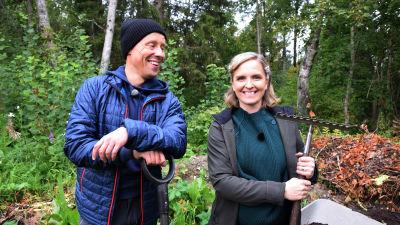 En man och en kvinna som står framför en hög med trädgårdsavfall och hållar i en spade och en kratta.