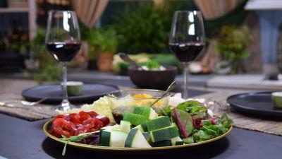 Dukning i ett kök med färdigt skurna grönsaker på ett fat
