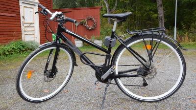 En svart hybridcykel av dammodell som står parkerad på en grusplan.
