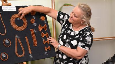 Berit Bragge pekar på en svart tavla där hennes stickade smycken av koppartråd hänger.