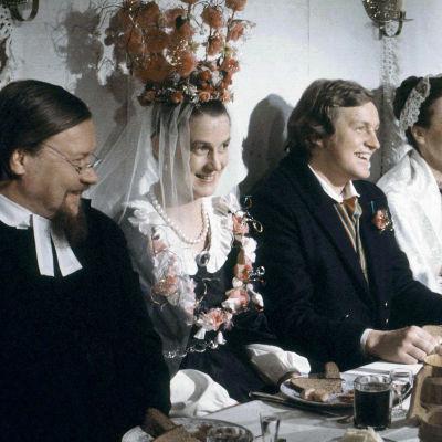 Pöydän ääressä istuu hääseurue sarjasta Myrskyluodon Maija. Morsiamen päässä on kruunu, joka on koristeltu ruusuin. Hänen kaulassaan on kukista tehty koru. Kuvassa on myös
