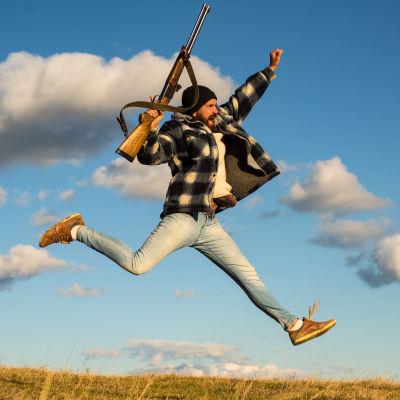Man med jaktkläder och gevär hoppar högt i luften