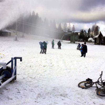 Lumitykki ampuu lunta rinteeseen.