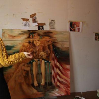 Emma Ainala viimeistelee maalaustaan.