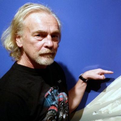 Lauri Nykopp osoittaa huiputtamatonta vuorenhuippua Grönlannin jäätiköllä. Teos on nimeltään Unclimbed #1.