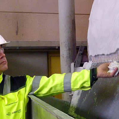 Tehtaanjohtaja Jukka Vehviläinen pitelee kädessään lasihiekkaa.