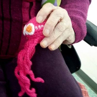 Virkattu mustekala vanhuksen kädessä