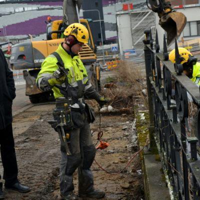 Rakennusmiehet irrottavat Porrassalmen valurauta-aitaa puhdistettavaksi Mikkelissä.