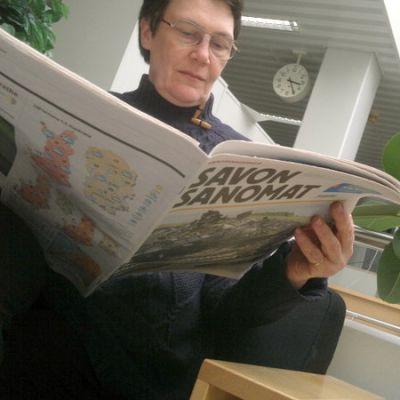 Nainen selaa tabloidikokoista sanomalehteä.