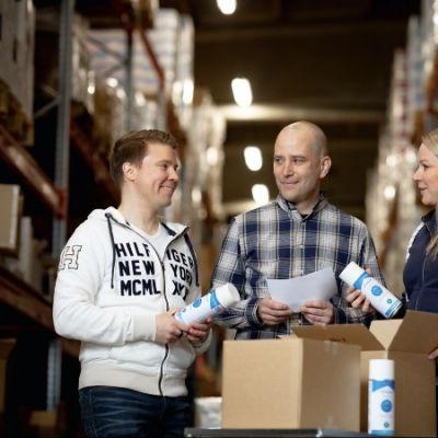 Kolme ihmistä katsoo varastossa desinfioivaa suihketta.