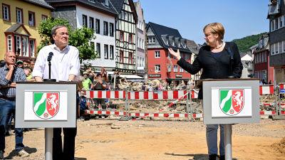 Till höger Angela Merkel och till vänster Armin Laschet. Bakom dem rödvit avspärrning och längst bort i bakgrunden en rad med hus.