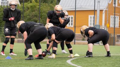 Spelare på gräsplan hukar sig för att ta tag i en amerikansk fotboll.