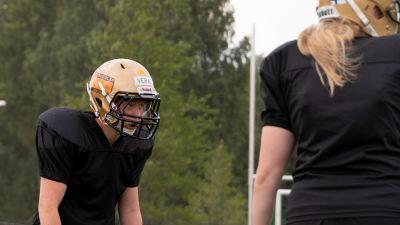 Två amerikansk fotboll-spelare i hjälm och svarta kläder på en gräsplan.