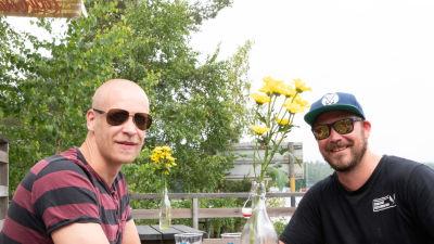 Två människor med solglasögon och blommor.
