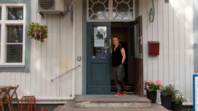 Ett gammlat vitt trähus, i dörröppningen står en kvinna.
