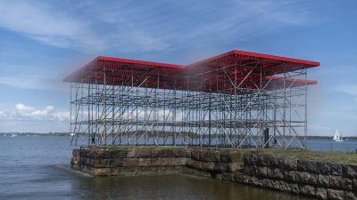 En stor konstruktion av byggnadsställningar och röd plattform vid kajen på Skanslandet.