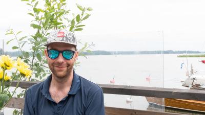 En man med solglasögon vid en hamn.