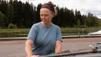 Kvinna vid mattvättnignsställe med en å i bakgrunden.