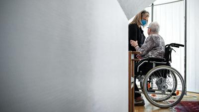 En person i munskydd hjälper en äldre person i rullstol.