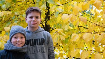 Två pojkar står utomhus med gula löv i bakgrunden.