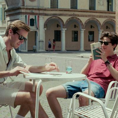 Oliver (Armie Hammer) och Elio (Timothée Chalamet) sitter vid en utomhusservering och pratar.