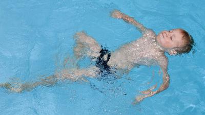 En pojke simmar ryggsim i en pool.