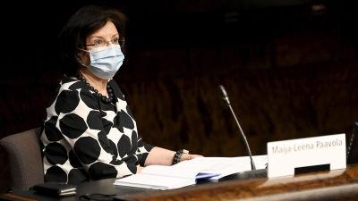 Kvinna med mörkt hår, munskydd och svartvitmönstrat plagg bakom en desk och en mikrofon i  Riksdagens generalsekreterare Maija-Leena Paavola på en presskonferens i Helsingfors den 29 juni 2021.
