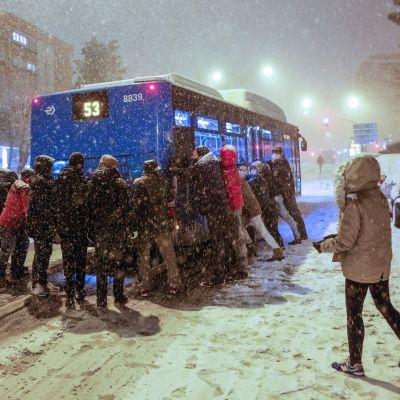 Ihmiset yrittävät saada lumihankeen juuttunutta bussia liikkeelle Madridissa Espanjassa.