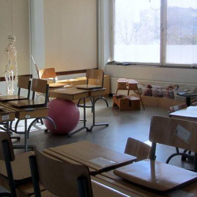 Tyhjiä pulpetteja luokkahuoneessa.