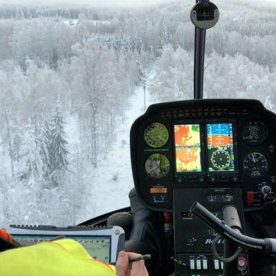Helikopteri lentää sähkölinjan yllä.