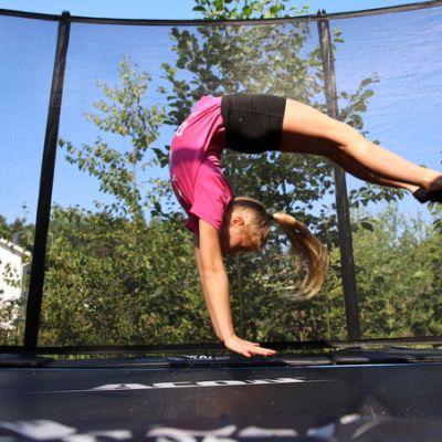 Tyttö hyppää taaksepäin trampoliinilla.