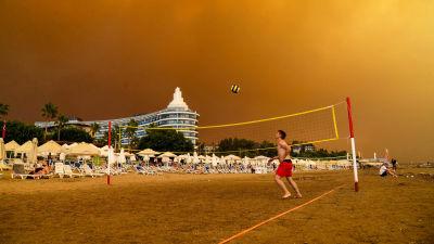 Någon spelar volleyboll på en strand i Turkiet. Himlen är orange och full av rök.