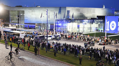 Eduskuntatalon edessä on Elokapinan mielenosoittajia ja poliiseja laajassa yleiskuvassa.