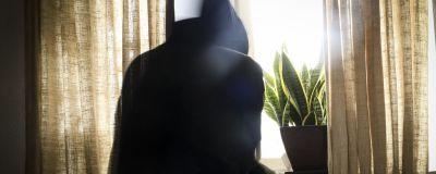 En person i munkjacka tittar ut genom fönstret, på fönsterbrädet står en krukväxt.