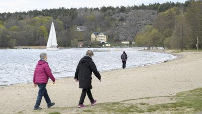 Människor promenerade längs en strand i Sätra, i sydöstra Stockholm den 25 april.