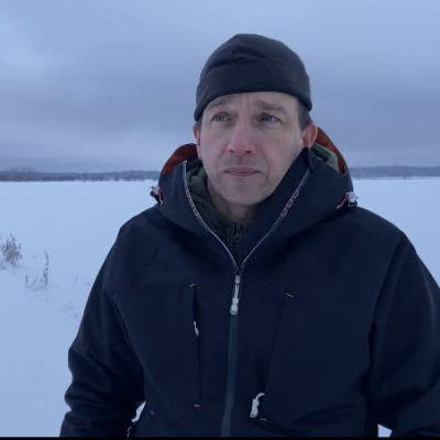 Mies seisoo talvisessa maisemassa