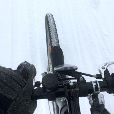 Ihminen pyöräilee pitäen yhdellä kädellä kiinni ohjaustangosta.