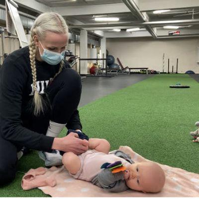 Äiti Laura Lehtilä vaihtaa vaippoja vauvalleen kuntosalin lattialla.