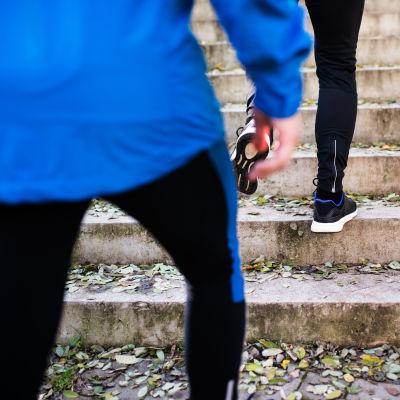 Två personer springer upp för trappor