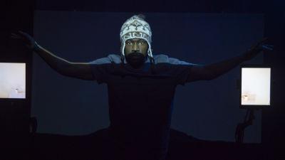 En man i en ljus mössa står på en mörk scen, ett hårt ljus framifrån lyser upp övre halvan av hans ansikte.