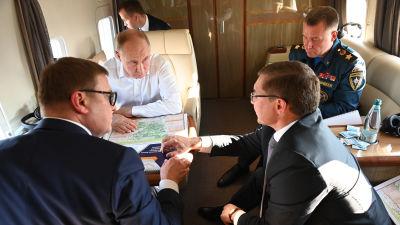 Vladimir Putin sitter i ett privatplan med katastrofminister Jevgeni Zinitjev och andra ministrar.