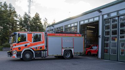 En brandbil kör ut från en brandstation.