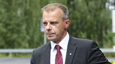 Centerns gruppordförande Juha Pylväs iklädd kostym och vinröd slips. i bakgrunden gröna lummiga träd.