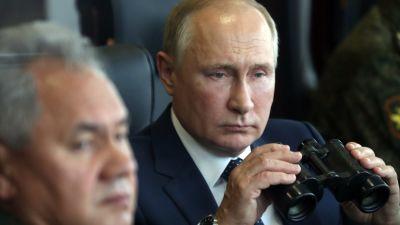Rysslands president Vladimir Putin spanar med kikare i handen.