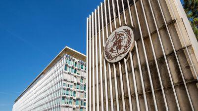 WHO:s högkvarter fotograferad nedifrån. På fasaden finns WHO:s cirkelformade logotyp med en lagerkrans, en karta över världen och symbolen för läkekonsten, en stav omslingrad av en orm.