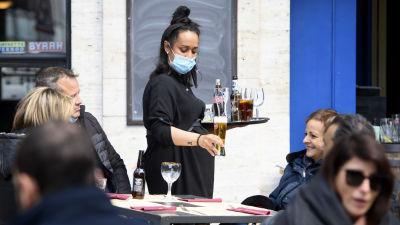 En kvinnlig servitör håller i en bricka med öl på en uteservering. Hon har munskydd på sig.