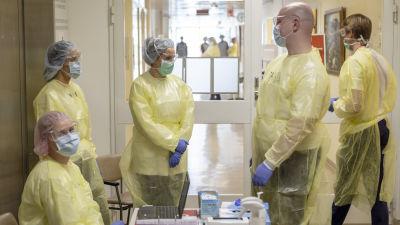 Sjukvårdare klädda i skyddsutrustning väntar på patienter vid hälsovårdsstationen i Dal i Helsingfors.