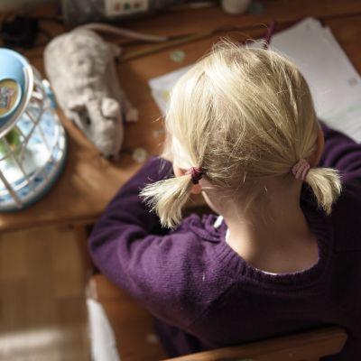 Ett barn sitter och ritar.